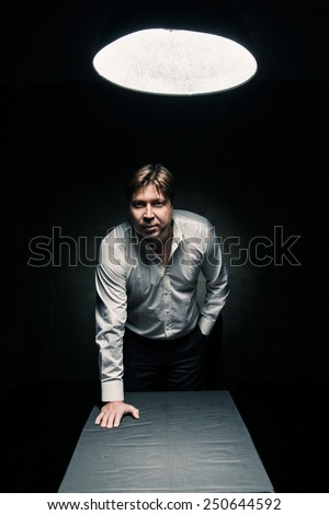 Man standing in dark room illuminated only by light from a lamp and looking in camera, hand on table - stock photo