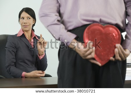 Man standing in front of a businesswoman and hiding a heart shaped gift behind his back.