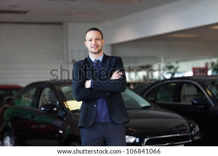 Man standing in front of a car in a dealership - stock photo