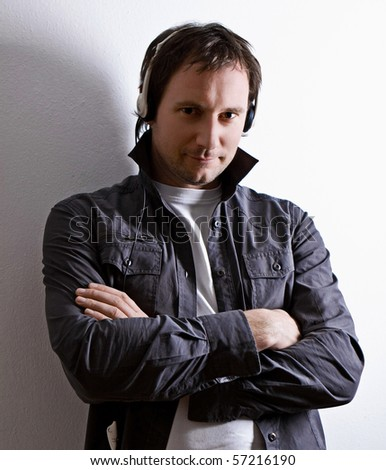 man standing in front of a wall listening to music - stock photo