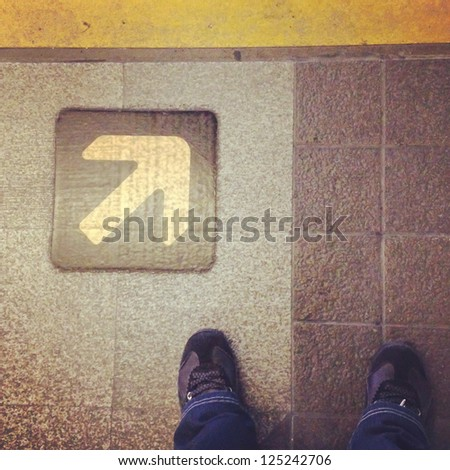 Man standing in front of direction signs. - stock photo