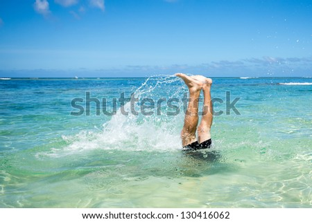 Man standing in handstand under water - stock photo