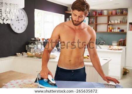 Man Standing In Kitchen Ironing Shirt - stock photo