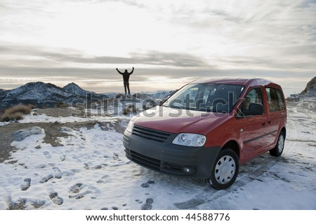 Man standing in snowed landscape with his car - stock photo