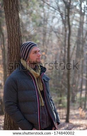 Man standing in the forest during wintertime with a thick jacket - stock photo