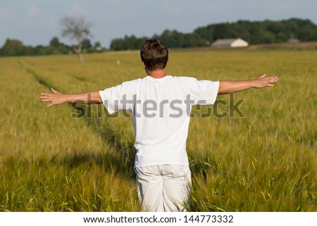 Man standing in wheat field with arms outstretched - stock photo