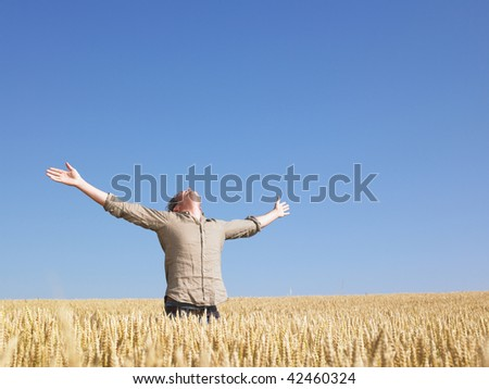 Man standing in wheat field with arms outstretched. Horizontally framed shot. - stock photo
