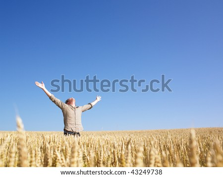 Man standing in wheat field with arms outstretched. Horizontally framed shot.