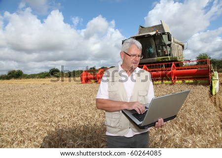 Man standing in wheat field with computer - stock photo