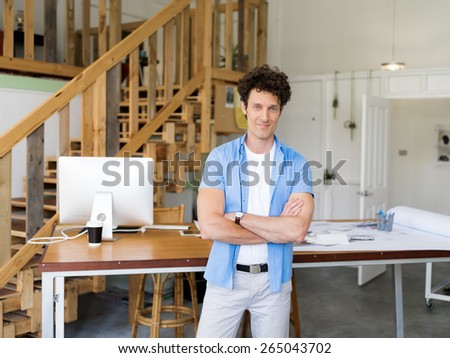 Man standing next to his desk in office