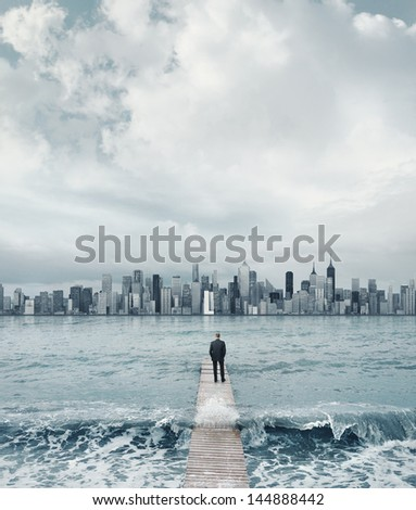 man standing on a boardwalk and looking at the city on a horizon - stock photo