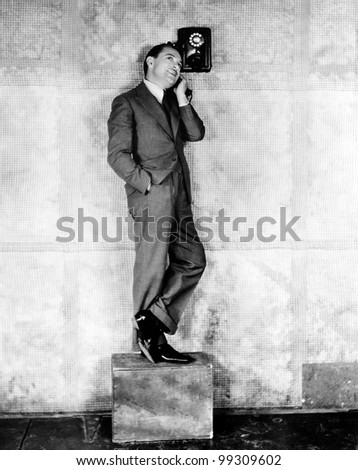 Man standing on a box to reach the telephone
