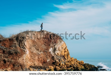 man standing on a cliff and looking at the sea