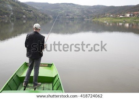 Man Standing On A Green Boat With His Back Towards The Camera And Fishing On The Calm Lake  - stock photo