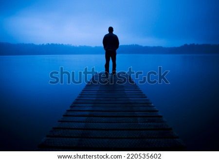 Man standing on a jetty by tranquil lake. - stock photo