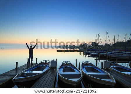 Man standing on a jetty in a marina during a foggy, autumn sunrise at a lake. - stock photo