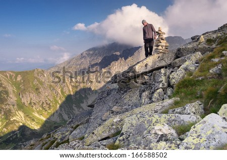 Man standing on a rock in the mountains and looking at bottom - stock photo