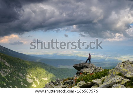 Man standing on a rock in the mountains and looks into the distance - stock photo