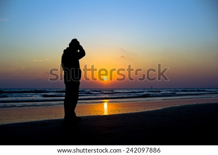 Man standing on a tropical beach at twilight silhouetted against a vivid orange ocean sunset with reflection across the surface of the sea - stock photo