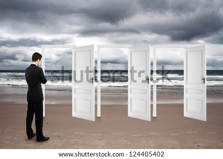 man standing on beach and opened doors - stock photo