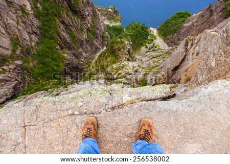 Man standing on cliff Preikestolen in fjord Lysefjord - Norway - nature and travel background - stock photo