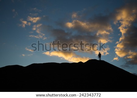 man standing on hill at sunset  - stock photo