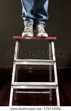 Man standing on ladder - stock photo