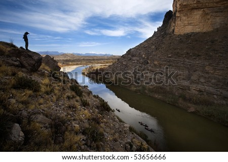 Man standing on large cliffs looking over river at canoes down in the water - stock photo