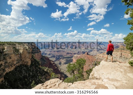 Man standing on rock overlooking the Grand Canyon National Park on the South Rim whilst on outdoor summer vacation holiday in the US - stock photo