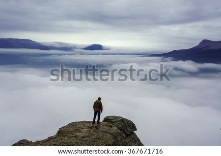 Man standing on rock's edge above the clouds - stock photo