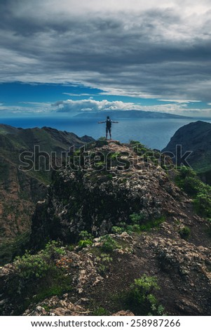 Man standing on the hill against background of the beautiful mountain landscape - stock photo