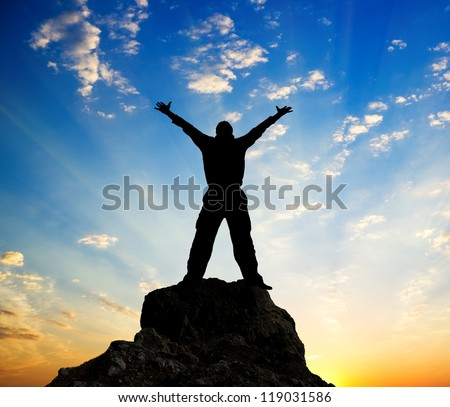 Man standing on top of a mountain.Silhouette of man and sunshine on sky background. greatness concept.