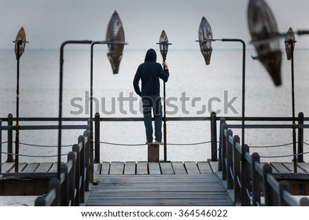Man standing on wooden pier looking over the sea, depression concept