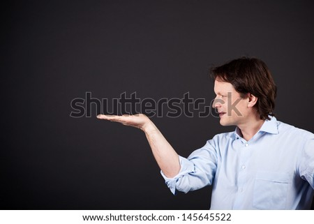 Man standing sideways holding out his empty palm for your product placement and advertising on a dark background - stock photo
