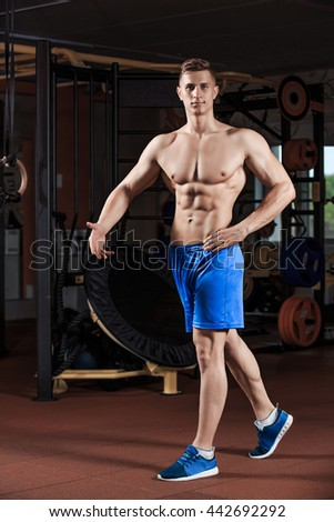 Man standing strong in the gym and flexing muscles