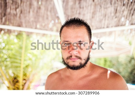 Man standing underneath sunshade made of palm trees   - stock photo
