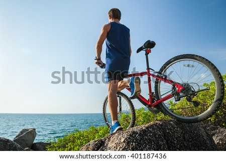 Man standing with a bicycle on the rock near sea - stock photo