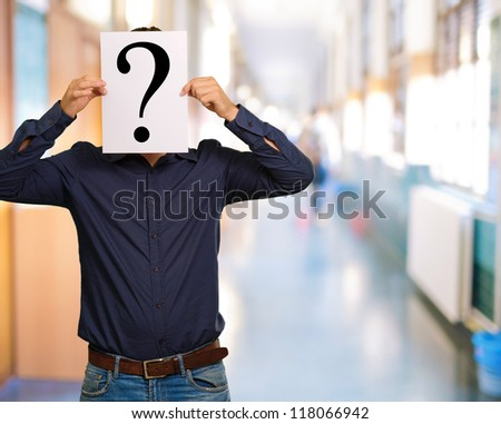 Man standing with a question mark board, outdoor - stock photo