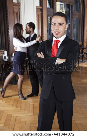 Man Standing With Arms Crossed While Dancers Performing Tango
