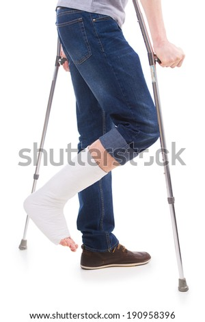 Man standing with crutches with bandage on broken leg. On white isolated - stock photo