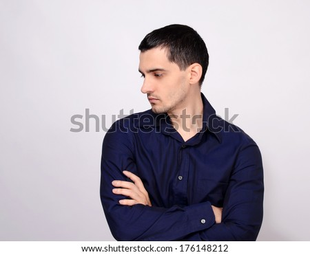Man standing with his arms crossed looking down over the shoulder to the side from profile. Portrait of a young business man wearing a dark blue shirt. - stock photo