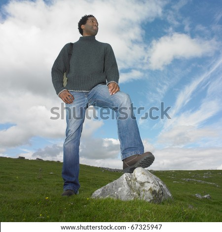 Man standing with one foot on a rock - stock photo