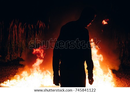 Man stands in front of flames of fire. Outdoor scene of the bonfire. Man standing near the camp fire.