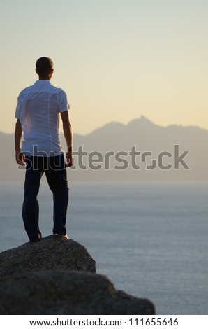 Man stands on a rock and looking at sea - stock photo