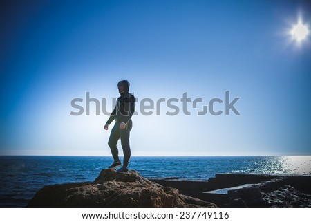 Man stands on a rock by the sea against the sky - stock photo