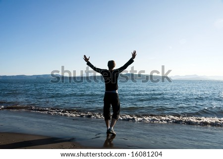 man stands on beach having stretched hands on sunset at night - stock photo