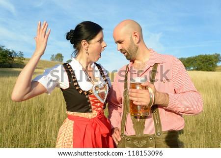 man staring at an angry woman in traditional bavarian garbs - stock photo