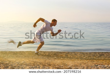 Man start running on the beach with the with the blue sky in the background and open space around him