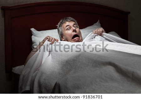 Man startled awake by intruder - stock photo