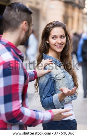 Man stops a beautiful woman on a street to take her number. He is touching her shoulder while she is standing half-turnded and smiles at him - stock photo